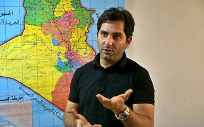 Raslan Haddad, the presenter of the local TV prank show, Tannab Raslan, stands in front of a map of Iraq during an interview with The Associated Press in Baghdad, Iraq, Tuesday, May. 5, 2021. (AP/Hadi Mizban)