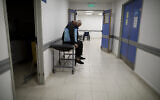 A man sits in a corridor as he waits for news of his wife who is suspected of having COVID-19 at the Dr. Norberto Raul Piacentini Hospital in Lomas de Zamora, Argentina, May 1, 2021. (AP Photo/Natacha Pisarenko)