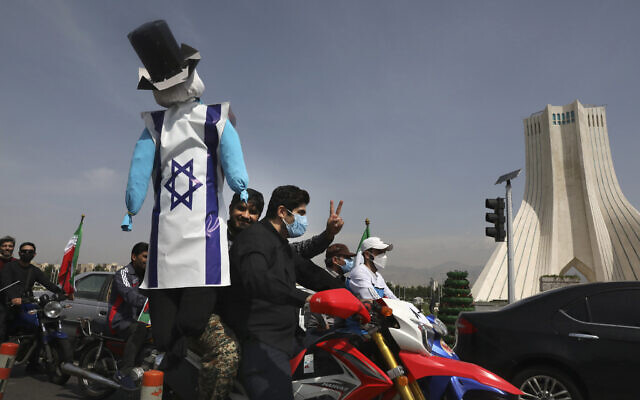 A demonstrator on a motorcycle holds an effigy representing Israel and the United States during the annual Al-Quds Day rally in Tehran, Iran, May 7, 2021  (AP Photo/Vahid Salemi)