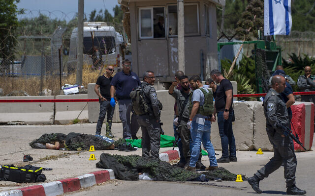 Israeli forces inspect the scene of a shooting attack where the bodies of two Palestinian gunmen, who were killed by Border Police after opening fire, lie on the ground in front of the military base of Salem near the West Bank town of Jenin, May 7, 2021. (AP Photo/Gil Eliyahu)
