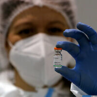 FILE - In this Jan. 19, 2021 file photo, a medical worker poses with a vial of the Sinopharm's COVID-19 vaccine in Belgrade, Serbia (AP Photo/Darko Vojinovic, file)