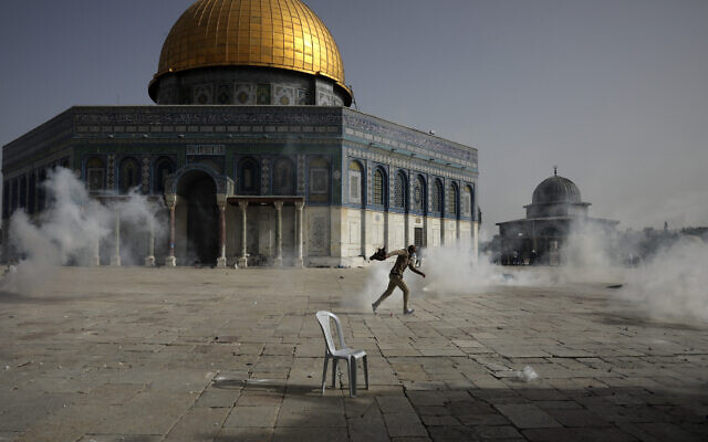 A Palestinian man runs away from tear gas during clashes with Israeli security forces in front of the Dome of the Rock Mosque at the Al Aqsa Mosque compound in Jerusalem's Old City, on May 10, 2021. (AP/Mahmoud Illean)