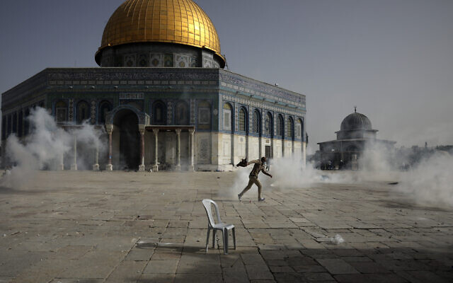 A Palestinian man runs away from tear gas during clashes with Israeli security forces in front of the Dome of the Rock Mosque in the Temple Mount compound in Jerusalem's Old City, May 10, 2021. (Mahmoud Illean/AP)