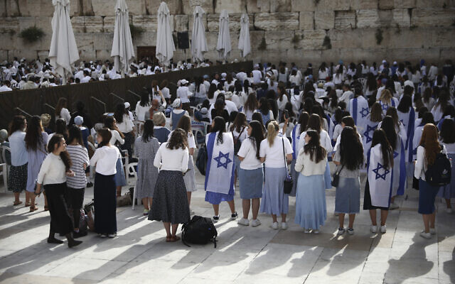 Jewish women, some covered with Israeli flags, pray during Jerusalem Day, an Israeli holiday celebrating the reunification of the city in the 1967 Six Day War, at the Western Wall, the holiest site where Jews can pray in the Old City of Jerusalem, May 10, 2021. (AP Photo/Oded Balilty)