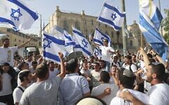 Israelis wave national flags during a Jerusalem Day march, in Jerusalem, May 10, 2021. (AP Photo/Ariel Schalit)