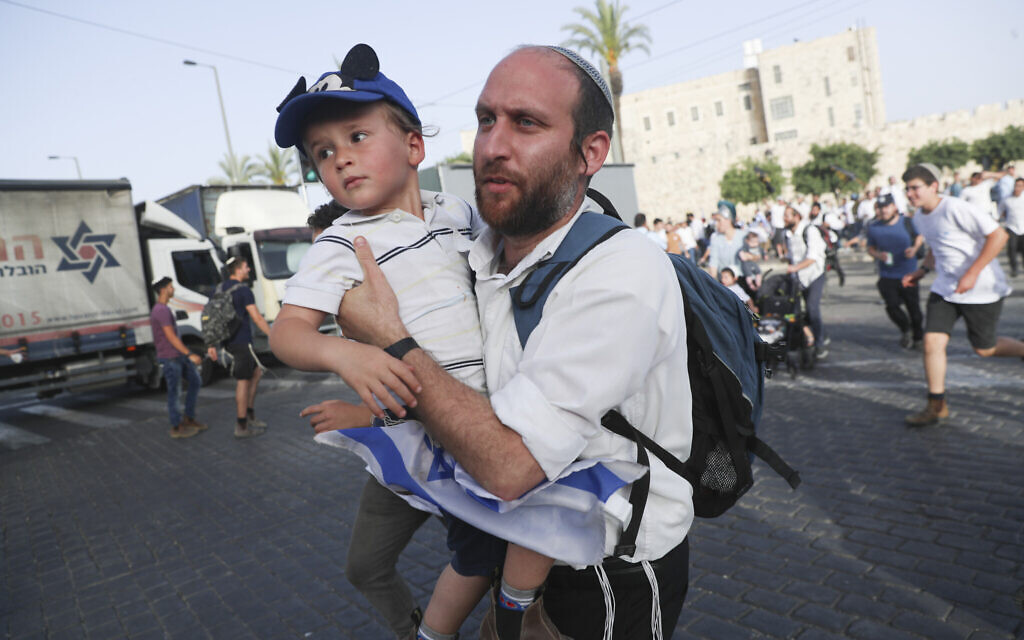 Israelis run for shelter as air attack sirens goes off during a Jerusalem Day march, in Jerusalem, Monday, May 10, 2021. (AP/Ariel Schalit)