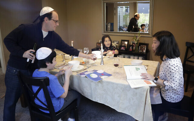 Seth Pollack pours wine for his family, wife Jessica Choe and children Micah and Mina Pollack, as they being their Passover meal in Seattle, April 8, 2020 (AP Photo/Elaine Thompson)