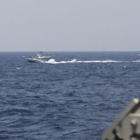 "In this image provided by the US Navy, an Iranian Islamic Revolutionary Guard Corps Navy (IRGCN) fast in-shore attack craft (FIAC), a type of speedboat armed with machine guns, speeds near US naval vessels transiting the Strait of Hormuz, May 10, 2021. US officials say a group of 13 armed speedboats of Iran's Revolutionary Guard made ""unsafe and unprofessional"" high-speed maneuvers toward US Navy vessels in the Strait of Hormuz. A U.S. Coast Guard cutter fired warning shots when two of the Iranian boats came dangerously close. (US Navy via AP)"