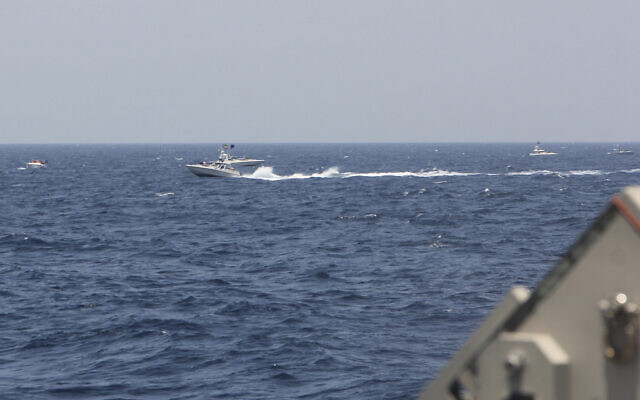"""In this image provided by the US Navy, an Iranian Islamic Revolutionary Guard Corps Navy (IRGCN) fast in-shore attack craft (FIAC), a type of speedboat armed with machine guns, speeds near US naval vessels transiting the Strait of Hormuz, May 10, 2021. US officials say a group of 13 armed speedboats of Iran's Revolutionary Guard made """"unsafe and unprofessional"""" high-speed maneuvers toward US Navy vessels in the Strait of Hormuz. A U.S. Coast Guard cutter fired warning shots when two of the Iranian boats came dangerously close. (US Navy via AP)"""