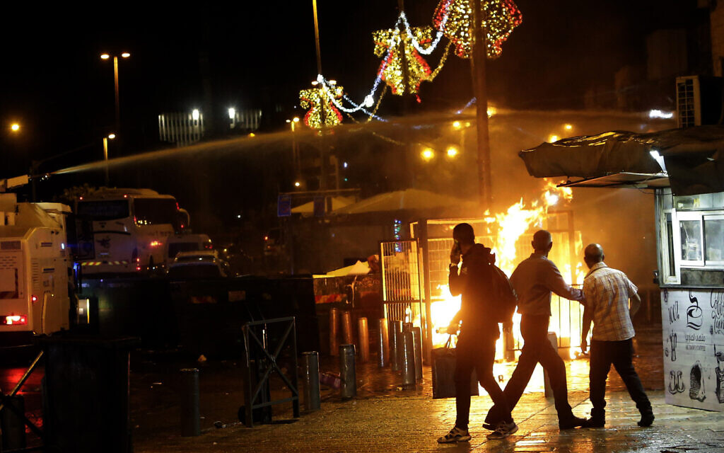 An Israeli police water cannon is deployed near the Damascus Gate to the Old City of Jerusalem as a fire burns during clashes between police and Palestinian protesters Monday, May 10, 2021. (AP Photo/Mahmoud Illean)