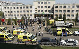Ambulances, police cars and a truck are parked at a school after a shooting in Kazan, Russia, May 11, 2021. (AP Photo/Roman Kruchinin)