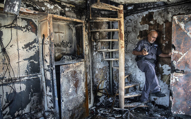 Avi Korkas examines the damage to a municipality office that was torched in a night of violence between Arab Israeli protesters and Israel Police in the city of Lod, May 11, 2021. (AP Photo/Heidi Levine)