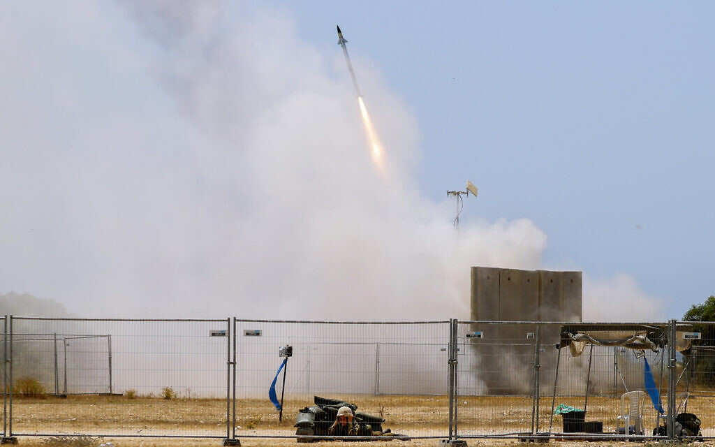 A Israeli soldier takes cover as an Iron Dome air defense system launches to intercept a rocket from the Gaza Strip, in southern Israel, May 11, 2021. (AP Photo/Ariel Schalit)