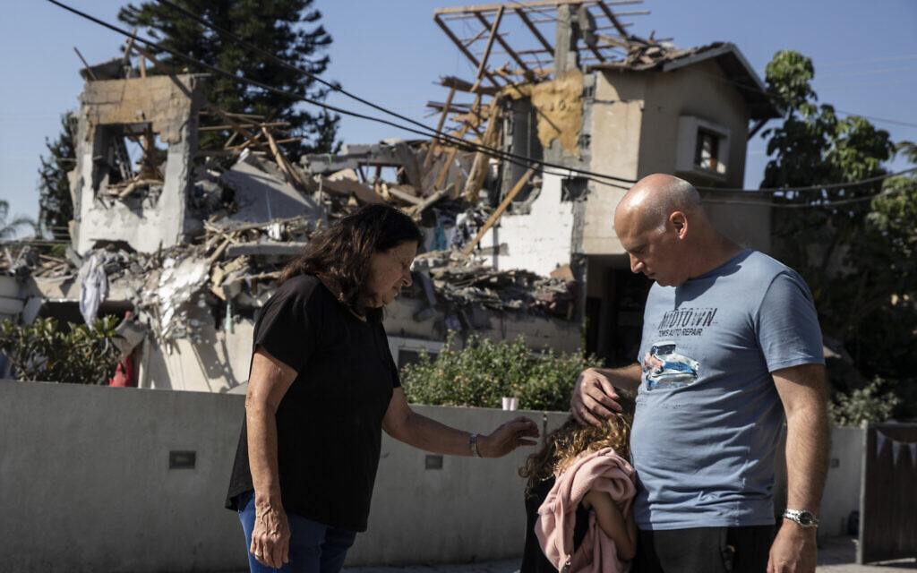 A young girl is comforted by her father next to a house damaged by a rocket fired from the Gaza Strip, in Yehod, central Israel, May 12, 2021 (AP Photo/Heidi Levine)