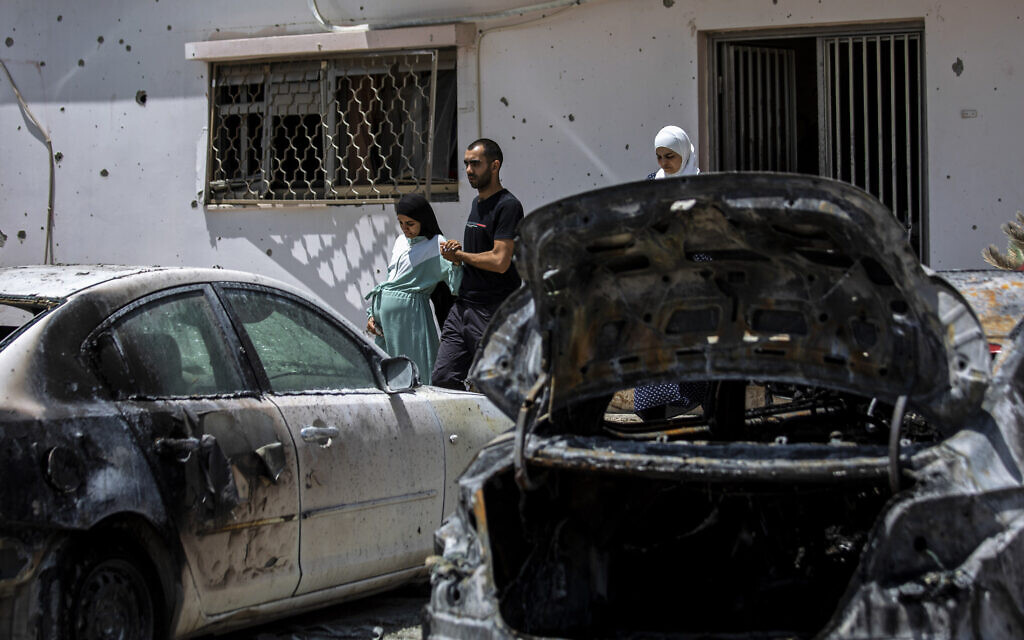 Relatives walk out of the damaged home of Nadine, 16, and Khalil Awaad, a father and daughter who were killed by a rocket fired from the Gaza Strip, in their village of Dahmash, May 12, 2021. (AP Photos/Heidi Levine)