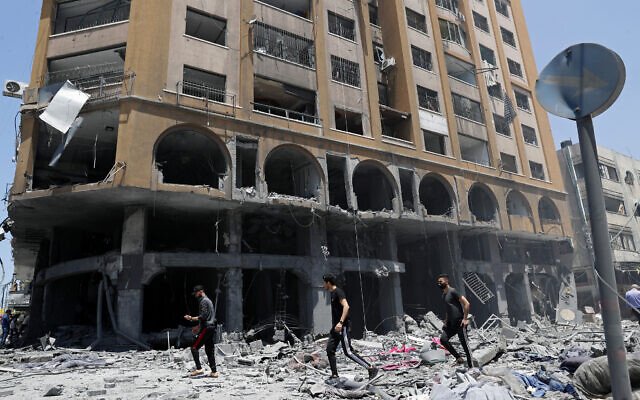 People inspect the rubble of a damaged building which was hit by an Israeli airstrike after heavy rocket fire from the Strip, in Gaza City, May 12, 2021. (AP Photo/Adel Hana)