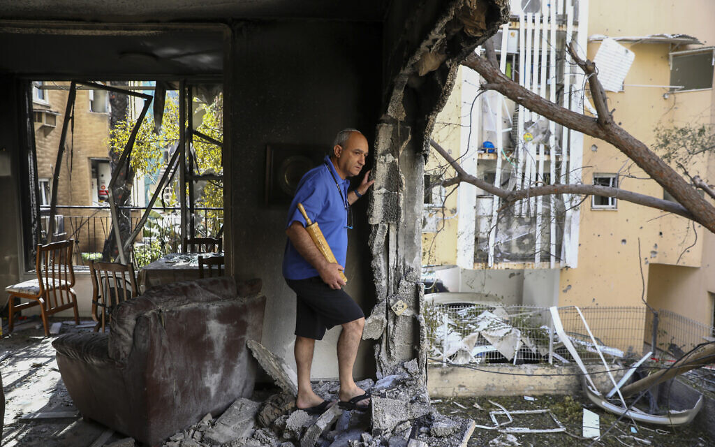 A member of Sror family inspect the damage of their apartment after being hit by a rocket fired from the Gaza Strip over night, in Petah Tikva, central Israel, May 13, 2021. (AP Photo/Oded Balilty)