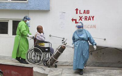 Paramedics take a COVID-19 patient to a ward after doing an X-ray at a government-run hospital in Kathmandu, Nepal, May 12, 2021. (AP Photo/Niranjan Shrestha)