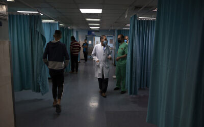 Palestinian doctors and medics walk inside the emergency room of the Shifa hospital in Gaza City, May 13, 2021. (AP/Khalil Hamra)
