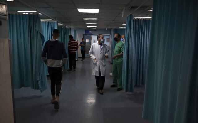 Palestinian doctors and medics walk inside the emergency room of the Shifa hospital in Gaza City, May 13, 2021. (AP/Khalil Hamra)