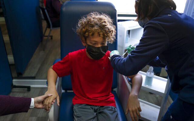 In Orange County, America, where teenagers are already receiving COVID-19 shots, Max Cuevas, 12, holds his mother's hand as he receives the Pfizer COVID-19 vaccine (AP Photo/Jae C. Hong)