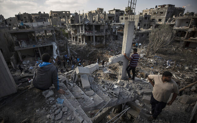 Palestinians inspect destroyed buildings following overnight Israeli airstrikes in Beit Hanoun, in the northern Gaza Strip, May 14, 2021. (AP Photo/Khalil Hamra)