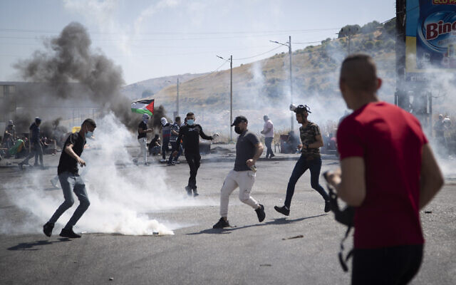 Palestinian protestors throw back a teargas canister during clashes with Israeli troops at the Hawara checkpoint, south of the West Bank city of Nablus, Friday, May 14, 2021. (AP Photo/Majdi Mohammed)