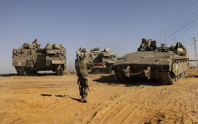 Israeli soldiers with armored vehicles gather in a staging ground near the border with Gaza Strip, southern Israel, Friday, May 14, 2021. (AP Photo/Tsafrir Abayov)