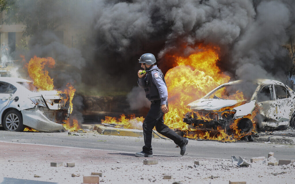 An Israeli firefighter walks next to cars hit by a missile fired from Gaza Strip, in the southern Israeli town of Ashkelon, Tuesday, May 11, 2021. (AP Photo/Ariel Schalit)