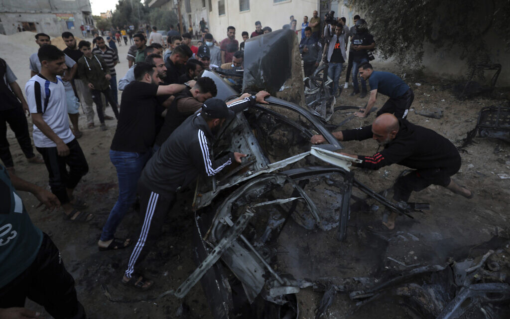 Palestinians gather around a car after it was hit by an Israeli airstrike in retaliation for rocket fire, in Gaza City, May 15, 2021. (AP Photo/Mohammed Ali)