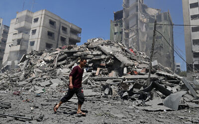 A man walks past the the rubble of the Yazegi residential building that was destroyed by an Israeli airstrike, in Gaza City, Sunday, May 16, 2021.  (AP Photo/Adel Hana)