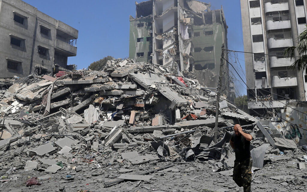 A man reacts while walking past the the rubble of the Yazegi residential building that was destroyed by an Israeli airstrike, in Gaza City, Sunday, May 16, 2021. (AP/Adel Hana)