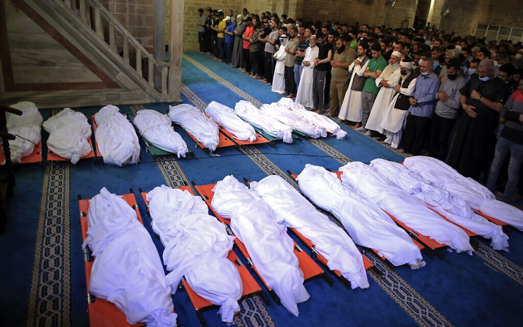 Mourners pray over the bodies of 17 Palestinians who were killed in overnight Israeli airstrikes in Gaza City, Sunday, May 16, 2021. (AP/Sanad Latifa)