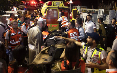 Israeli medics carry wounded ultra-Orthodox men outside a synagogue in Givat Zeev, outside Jerusalem, Sunday, May 16, 2021. More than 150 people were injured in a fatal collapse of a bleacher at an uncompleted West Bank synagogue.  (AP Photo/Sebastian Scheiner)