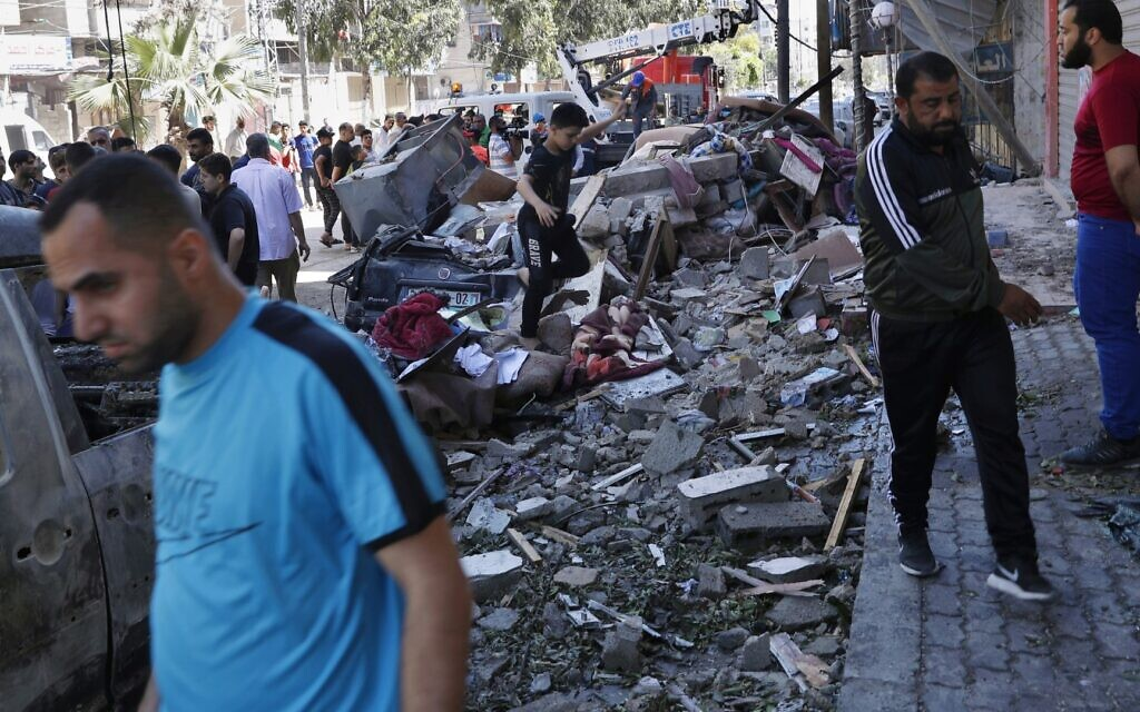 People inspect rubble of a destroyed building that was hit by an Israeli airstrike early morning, in Gaza City, Wednesday, May 19, 2021. (AP Photo/Adel Hana)