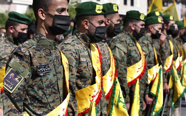 In this May 15, 2021 file photo, Hezbollah fighters attend the funeral procession of their comrade Mohammed Tahhan who was shot dead on Friday by Israeli forces along the Lebanon-Israel border, in the southern village of Adloun, Lebanon. (AP Photo/Mohammed Zaatari, File)
