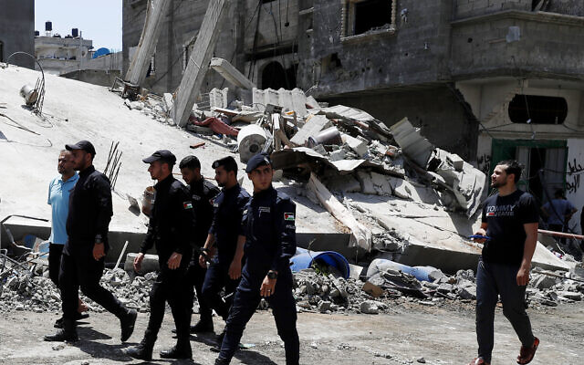 Police officers from Gaza's ruling Hamas terror group near a destroyed residential building which was hit by Israeli airstrikes after rocket fire from Gaza, in Beit Lahiya, Gaza Strip, Thursday, May 20, 2021. (AP/Adel Hana)