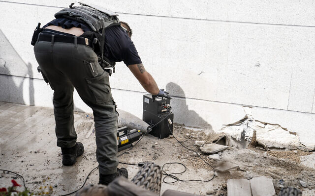 A technician inspects an unexploded missile fired from the Gaza Strip that landed on the top floor of a high rise apartment building, May 20, 2021, in Ashkelon, southern Israel. (AP Photo/John Minchillo)