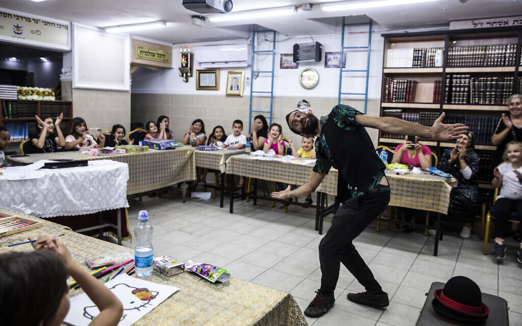 Israeli juggler Guy Kaplan performs for children in a bomb shelter, following rocket attacks fired from the Gaza Strip, in Ashdod, Israel,  May 20, 2021. (AP Photo/Heidi Levine)