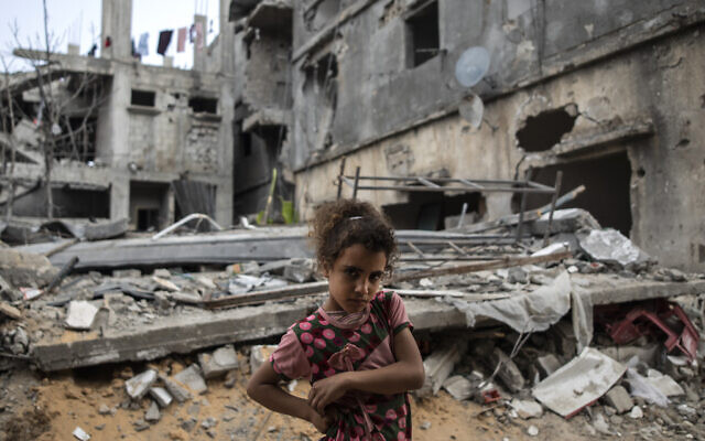 Palestinian Rahaf Nuseir, 10, looks on as she stands in front of her family's destroyed homes, to which they returned following a cease-fire reached after an 11-day war between Gaza's Hamas rulers and Israel, in town of Beit Hanoun, northern Gaza Strip, Friday, May 21, 2021. (AP/Khalil Hamra)