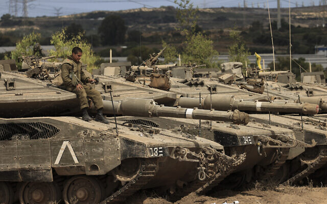 An Israeli soldier sits on top of a tank at a staging ground near the border with Gaza Strip, southern Israel, May 21, 2021. (AP Photo/Tsafrir Abayov)