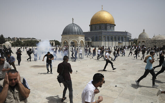 Palestinians run from sound bombs thrown by Israeli police in front of the Dome of the Rock shrine at the al-Aqsa mosque complex in Jerusalem, Friday, May 21, 2021. (AP Photo/Mahmoud Illean)
