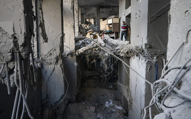 People enter the severely damaged Al-Jawhara building to salvage valuable items following a cease-fire reached after an 11-day war between Gaza's Hamas rulers and Israel, in Gaza City, Friday, May 21, 2021. (AP Photo/John Minchillo)