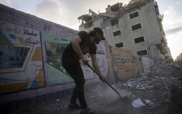 People clean the streets of debris beside a building that was previously damaged in an air-strike following a cease-fire reached after an 11-day war between Gaza's Hamas rulers and Israel, in Gaza City, May 21, 2021. (AP Photo/John Minchillo)