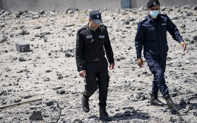 Hamas police walk through debris from a destroyed building that was hit by an airstrike previous to a ceasefire reached after an 11-day war between Gaza's Hamas rulers and Israel, in Gaza City, Saturday, May 22, 2021. (AP Photo/John Minchillo)
