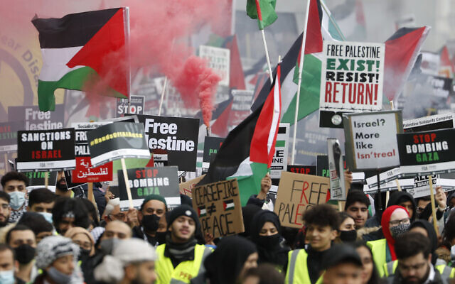 Protesters hold placards and banners in London, May 22, 2021, as they take part in a rally supporting Palestinians. (AP Photo/Alastair Grant)