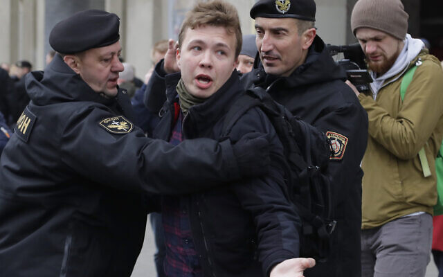 In this March 26, 2017 file photo, Belarus police detain journalist Raman Pratasevich, center, in Minsk, Belarus. Raman Pratasevich, a founder of a messaging app channel that has been a key information conduit for opponents of Belarus' authoritarian president, has been arrested after an airliner in which he was riding was diverted to Belarus because of a bomb threat. . (AP Photo/Sergei Grits, File)