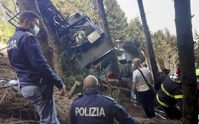 Rescuers work by the wreckage of a cable car after it collapsed near the summit of the Stresa-Mottarone line in the Piedmont region, northern Italy, Sunday, May 23, 2022. (Italian Police via AP)