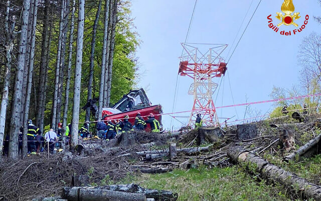 Rescuers work by the wreckage of a cable car after it collapsed near the summit of the Stresa-Mottarone line in the Piedmont region, northern Italy, Sunday, May 23, 2022. (Italian Vigili del Fuoco Firefighters via AP)