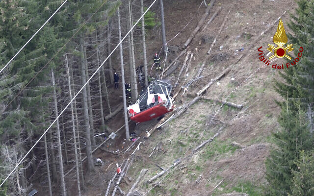 Rescuers work by the wreckage of a cable car after it collapsed near the summit of the Stresa-Mottarone line in the Piedmont region, northern Italy, as seen from the aerial photograph, May 23, 2021. (Vigili del Fuoco Firefighters via AP)